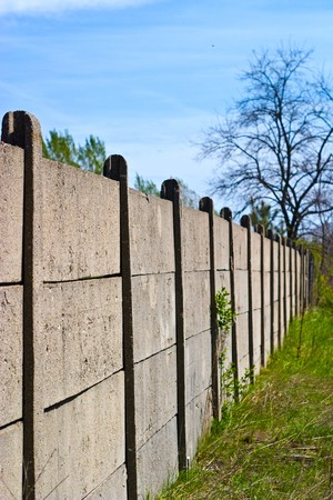 Old concrete boundary fence with nails on sunny day Stock Photo - 6936470