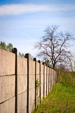 Old concrete boundary fence with nails on sunny day Stock Photo - 6936251
