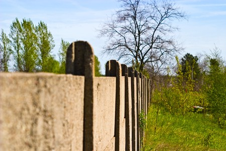 Old concrete boundary fence with nails on sunny day
