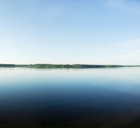 A rural blue lake and a green forest Stock Photo - 9723449
