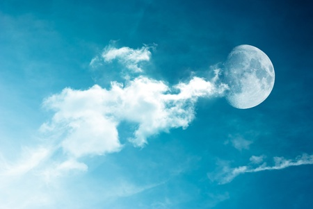 Moon between the clouds in dark night, a dark night brings a bright, amber moon alive with puffy hazy clouds. Stock Photo - 11386038