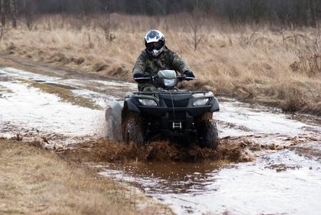 male riding a quad, four wheeler in rural, sport series Editorial