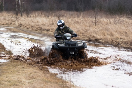 male riding a quad, four wheeler in rural, sport series Imagens