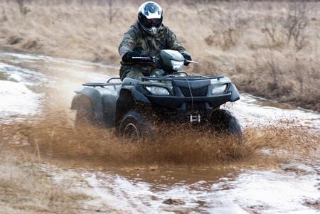 male riding a quad, four wheeler in rural, sport series Standard-Bild