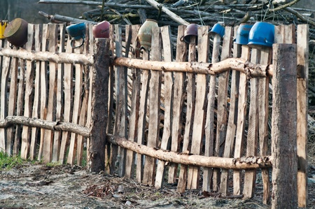 Old wooden boundary fence with nails on sunny day photo