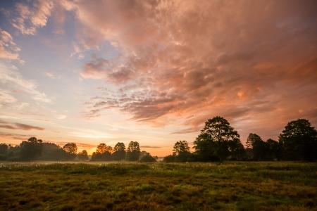 vorkommende gelbe Sonne hinter den Wolken an einem warmen Abend
