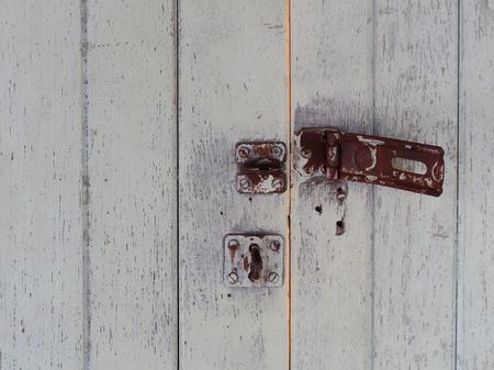 Old rusty door unlock with white wooden background