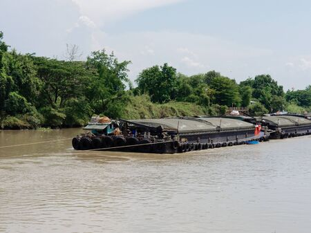 Ayutthaya, Thailand - May 14, 2018 : Heavy loaded barge pulled or towed by tugboat down Chao Phraya River with transportation and industry concept