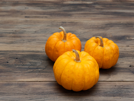 Three orange pumpkins in big, medium, and small size on dark wooden background show colorful pattern and scale used in Halloween, still life, kitchen, and comparison, and country themes