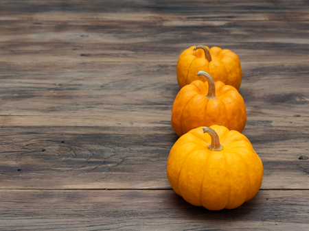 Three orange pumpkins in big, medium, and small size put vertically on dark wooden background show colorful pattern and scale used in Halloween, still life, kitchen, and comparison, and country themes