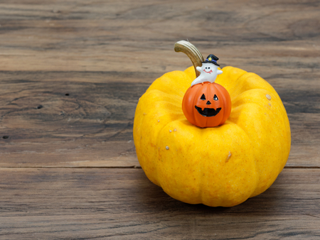 Yellow organic pumpkin and orange miniature ceramic pumpkin with white ghost on dark wooden background used in Halloween, still life, kitchen, and comparison, and country themes