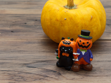 Close up shot of yellow organic pumpkin and orange miniature ceramic pumpkin guy with black cat on dark wooden background used in Halloween, still life, kitchen, and comparison, and country themes Stock Photo