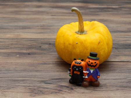 Yellow organic pumpkin and orange miniature ceramic pumpkin guy with black cat on dark wooden background used in Halloween, still life, kitchen, and comparison, and country themes