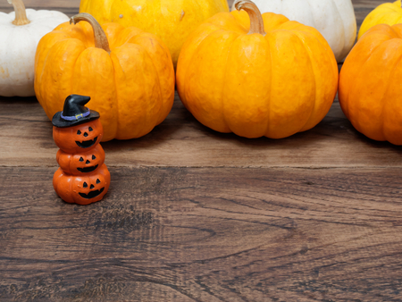 Three orange miniature ceramic pumpkin heads wearing black hat with white, yellow, and orange pumpkins on background over dark wooden surface with space used in Halloween, festival, and decoration Archivio Fotografico