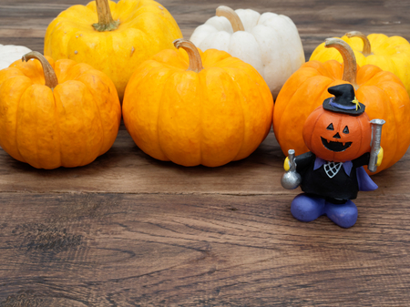 Orange miniature ceramic pumpkin head magician wearing black hat with white, yellow, and orange pumpkins on background over dark wooden surface with space used in Halloween, festival, and decoration