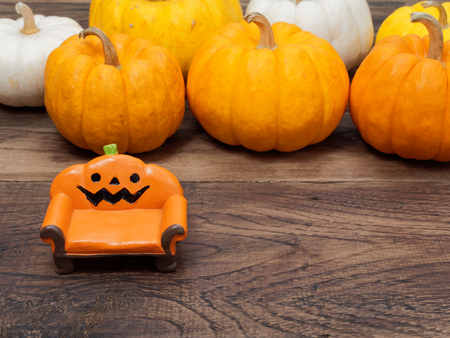 Orange miniature ceramic pumpkin couch or sofa with white, yellow, and orange pumpkins on the background over dark wooden surface with copy space used in Halloween, still life, kitchen, and decoration Archivio Fotografico
