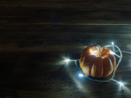 White decoration lights with yellow and orange pumpkins over dark wooden surface with space used as background, wallpaper, or backdrop in Halloween, festival, ornament and decoration theme Archivio Fotografico