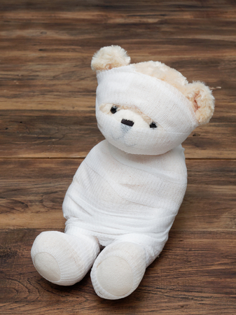 Portrait of cute mummy teddy bear doll bind with white gauze or bandage on dark wooden background used as background, wallpaper, or backdrop in Halloween, festival, and decoration theme