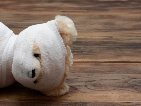 Headshot portrait of cute mummy teddy bear doll bind with white gauze or bandage on dark wooden background used as background, wallpaper, or backdrop in Halloween, festival, and decoration theme Archivio Fotografico