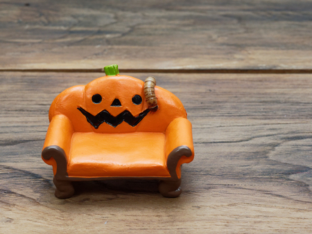 Super or giant worm crawling on orange miniature ceramic pumpkin couch or sofa over dark wooden surface with copy space used as background in Halloween, ornament, celebration, and decoration Stock Photo