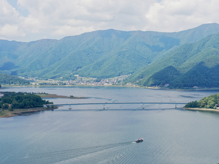 Scenery of Lake Kawaguchi, the biggest lake of Fuji five lakes, with a ferry boat and an overwater bridge crossing the lake and mt Kurodake on the background, famous tourist destination in Japan