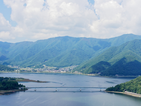 Scenery of Lake Kawaguchi, the biggest lake of Fuji five lakes, with an overwater bridge crossing the lake and mt Kurodake on the background, famous tourist destination in Japan Stock Photo