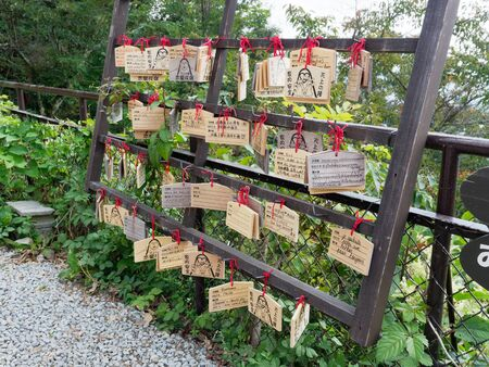 FUJIKAWAGUCHIKO, JAPAN - SEPTEMBER 26, 2017 : Wooden votive tablets or ema written in many languages wish for good luck and fortune hanged on wooden rail on Mt. Kachi kachi or kawaguchiko ropeway
