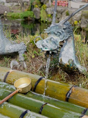 YAMANASHI, JAPAN - SEPTEMBER 26, 2017 : Spring water from dragon ornament tap of Waku pond is one of the main tourist attraction in Oshino Hakkai or springs of Mount Fuji, Oshino village Editoriali