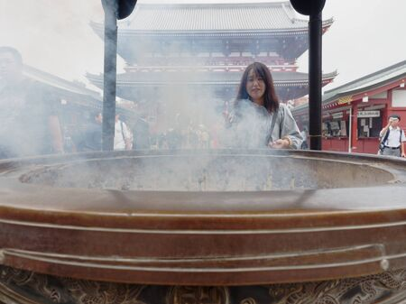 TOKYO, JAPAN - SEPTEMBER 28, 2017 : Gigantic bronze incense burner in front of Main Hall of Sensoji temple, Asakusa, where tourists bathing their hands and faces with incense smoke