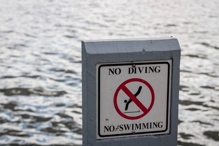 no swimming sign: No diving and no swimming sign with lake background. Stock Photo