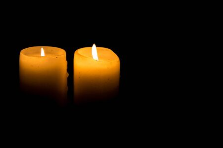 Two candles burning isolated on black.