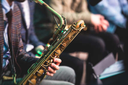 Concert view of a saxophonist, saxophone sax player with vocalist and musical during jazz orchestra performing music on stage
