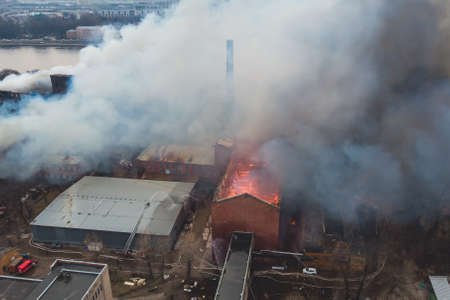 Massive large blaze fire in the city, aerial drone top view brick factory building on fire, hell major fire explosion flame blast, with firefighters team, arson, burning damage destruction Standard-Bild