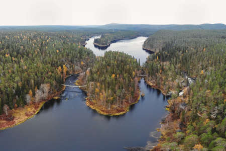 Autumn view of Oulanka National Park, landscape, a Finnish national park in the Northern Ostrobothnia and Lapland regions of Finland, wooden wilderness hut, cabin cottage, bridge, campground Standard-Bild