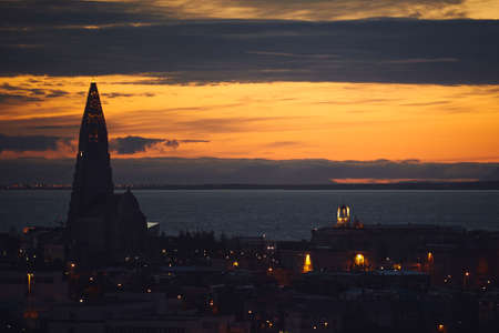Beautiful night dusk view of Reykjavik, Iceland, aerial view with Hallgrimskirkja lutheran church, with scenery beyond the city, Esja mountain and Faxafloi ocean bay