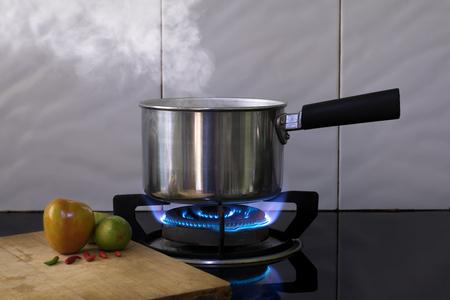 Heißer Dampf auf Metalltopf auf dem Flammgasherd zum Kochen von Wassersuppe.