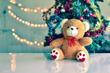 Teddy Bear wear hat in Christmas and Multi colored balls on christmas tree with Blur light Background.