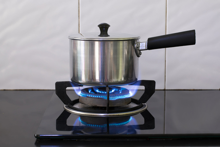 Metal pot on the flame gas stove for boiling water Soup. Foto de archivo