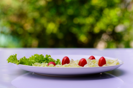 Salad on white table with a background blur bokeh.