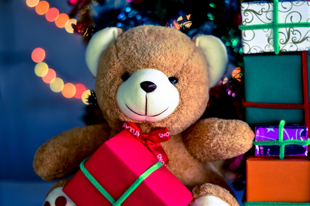 Teddy Bear in Christmas day and Gift Box with christmas tree with Blur light Background.