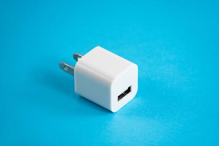 Smartphone Charger usb plug on blue background.