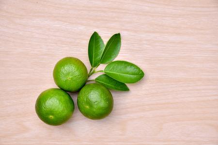 Green lemon on a wooden floor into the background. 版權商用圖片