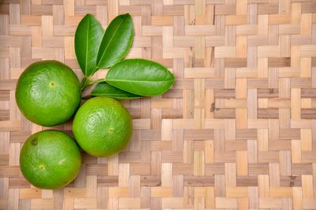 Green lemon on a basket into the background. 版權商用圖片