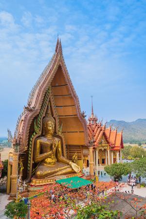 Wat Tham Sua, Kanchanaburi, Thailand - January 27, 2018 : Tham Sua Temple pagoda with golden Buddha statues set into the spotlight with the worship liturgy of people. 新聞圖片