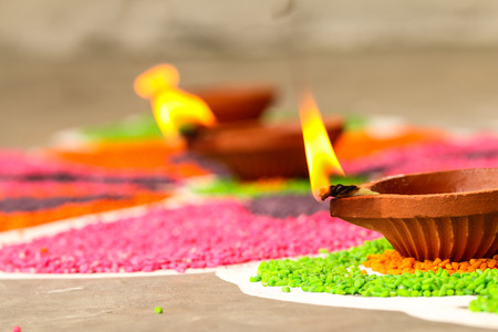 Traditional clay oil lamp, diwali oil lamp on colorful rangoli, kolam Stock Photo