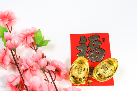 Chinese New Year decorations of yuan bao, cherry blossoms and Chinese caligraphy of the word Fook meaning wealth, good fortune and prosperity on red ang pow Stock Photo