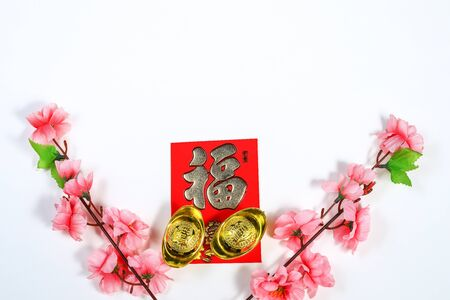 Chinese New Year decoration with cherry blossom, yuan bao and Chinese Caligraphy words of Fook meaning prosperity, wealth, lucky, on red ang pow