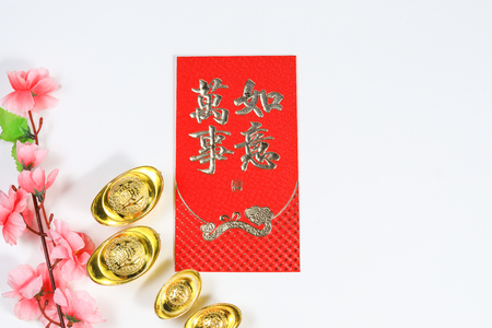 Chinese New Year decoration with yuan bao, cherry blossom and Chinese Caligraphy words of Fook and Wanshiruyi meaning prosperity, wealth, lucky, dreams comes true and success, on red ang pow