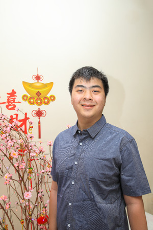 Ang pao, Asian young man in smart casual by the Chinese New Year decorations of Chinese characters Gong Xi Fa Cai, yuan bao, cherry blossom, Lunar New Year. Stock Photo