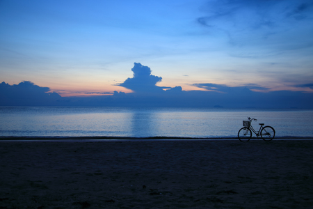 Beautiful serene blue hour before the sun rises at a beach with bicycle in the foreground Stock Photo